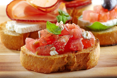 Spanish food tapas  Toasted bread with chopped tomato and basil Stock Photo - 28424635