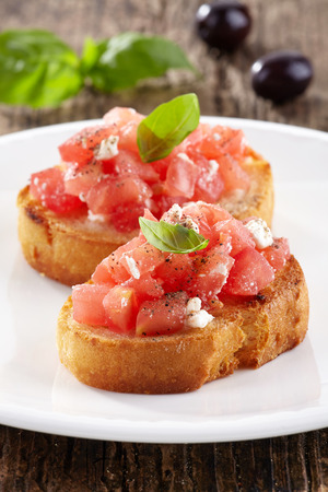 Spanish food tapas. Toasted bread with chopped tomato and basil photo
