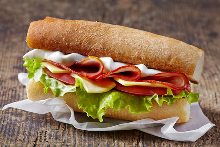 Sandwich with serrano ham and vegetables on wooden table