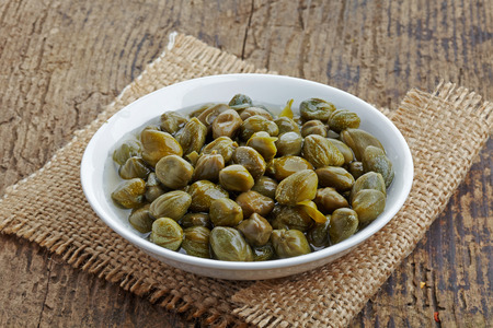 bowl of capers on wooden table photo