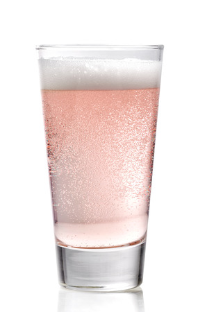 carbonated: Glass of pink cider on a white