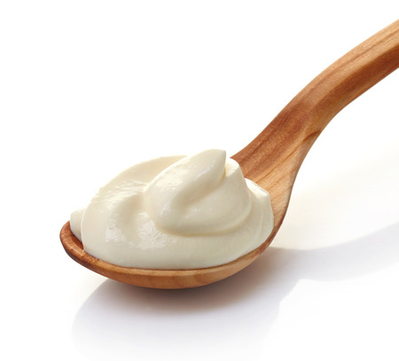 cream in a wooden spoon on a white background