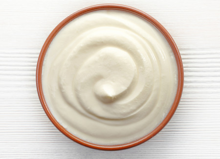 yogurt natural: tazón de crema en la mesa de madera blanca, vista desde arriba