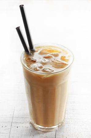 Glass of iced coffee with milk on white wooden table photo