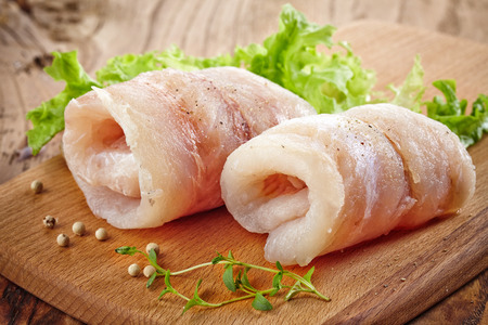 hake: raw hake fish fillet rolls on wooden cutting board