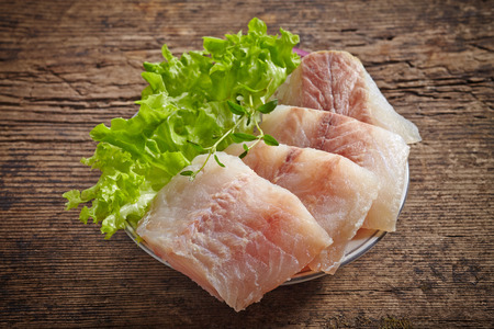 hake: raw hake fish fillet pieces on dark wooden table Stock Photo