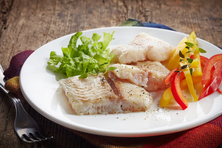 pangasius: fried pangasius fish fillet pieces on a white plate