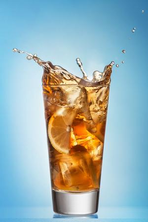 Glass of splashing iced tea with lemon on blue background photo