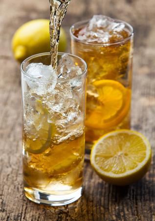 té helado: Verter el té helado con limón en vidrio, enfoque selectivo Foto de archivo