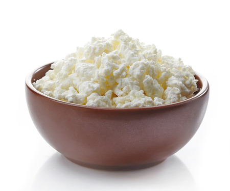 bowl of fresh cottage cheese on a white background