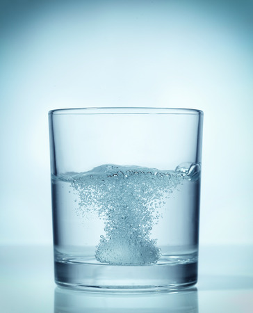 effervescent dissolving fizzy tablet in water glass photo
