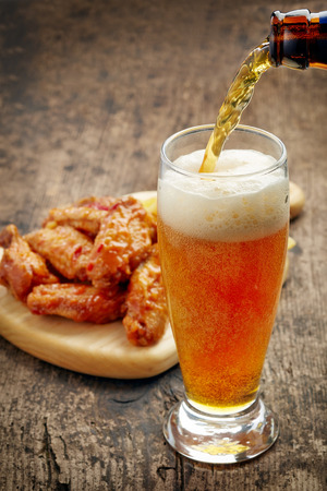 pouring beer: beer pouring into glass and fried chicken wings on wooden table Stock Photo
