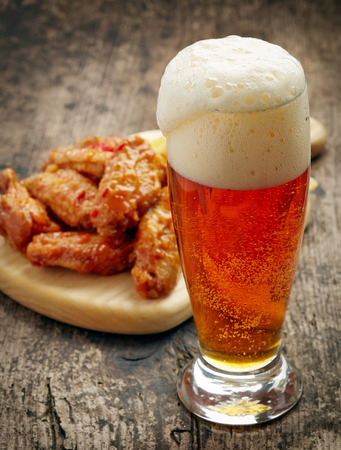 glass of fresh beer and fried chicken wings on wooden table photo