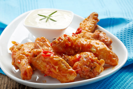 fried chicken wings with sweet chili sauce on white plate photo