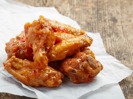 fried chicken wings with sweet chili sauce on white paper photo