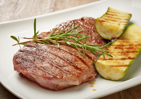 calabacin: filete de carne a la parrilla y calabacín en un plato blanco