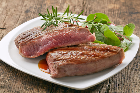 grilled beef steak with rosemary on white plate photo