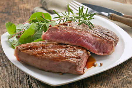 grilled beef steak with rosemary on white plate