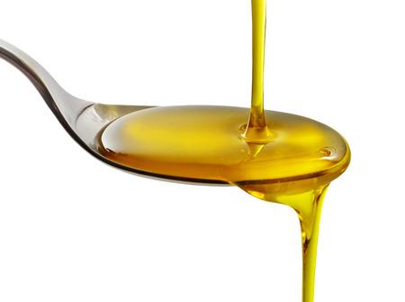 verser de l'huile de cuisson dans une cuillère sur un fond blanc Banque d'images