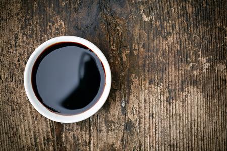 Kom van Balsamico azijn op houten tafel Stockfoto