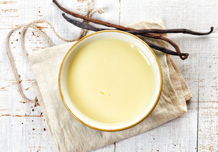 bowl of vanilla sauce on white wooden table, top view Stockfoto