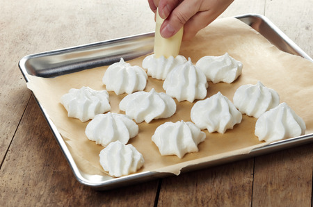 whipping: making meringue cookies on a cooking pan Stock Photo