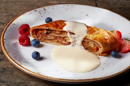 apple strudel with vanilla sauce and fresh berries photo