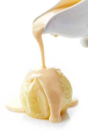 vanilla sauce pouring on baked apple on a white background Stock Photo