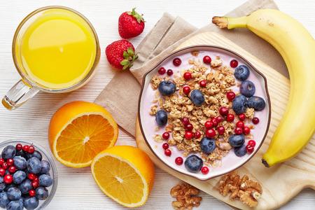 jugos: Desayuno saludable. Cuenco de yogur con granola y bayas