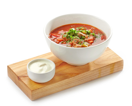 Bowl of goulash soup and sour cream served on wooden board photo