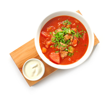 meat soup:  Bowl of goulash soup and sour cream served on wooden board Stock Photo