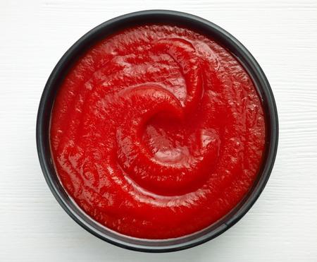 salsa de tomate: taz�n de salsa de tomate o salsa de tomate en la mesa de madera blanca