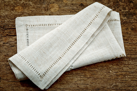 fabric cotton: folded linen napkin on old wooden table