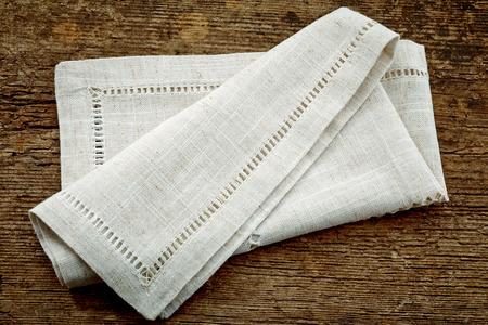 serviette: servilleta de lino plegado en mesa de madera vieja