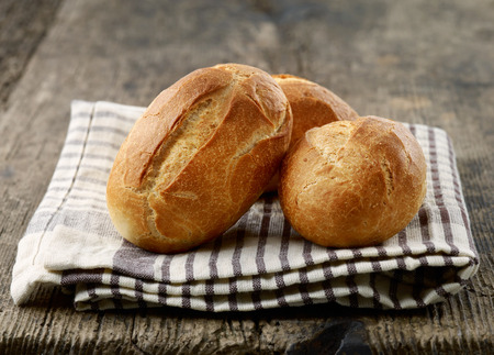 古い木製のテーブルで焼きたてのパンのパン