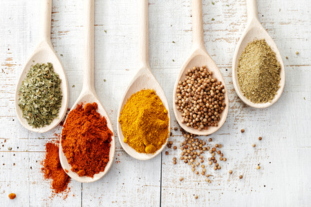 kitchen background: various spices in wooden spoons on old white wooden table