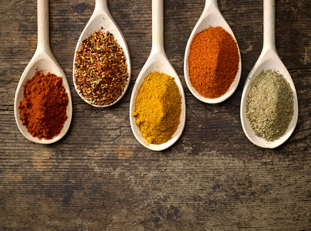 chili powder: various kinds of spices in wooden spoons