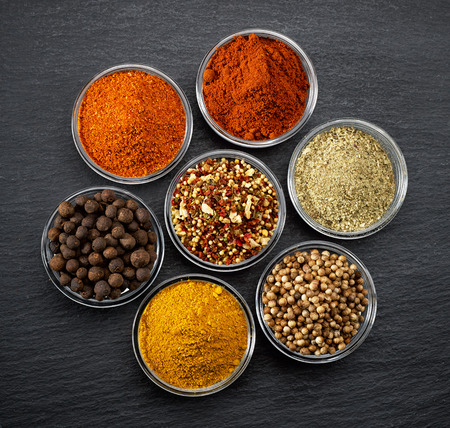 stone bowl: various kinds of spices on black stone surface Stock Photo