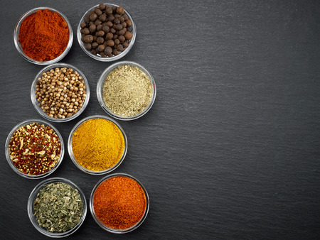 various kinds of spices on black stone surface Stock Photo