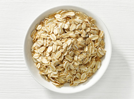 bowl of cereal: bowl of oat flakes on white wooden table
