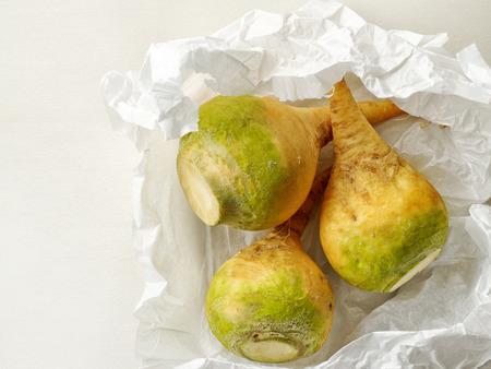 rutabaga: Fresh raw rutabaga on white wrapping paper