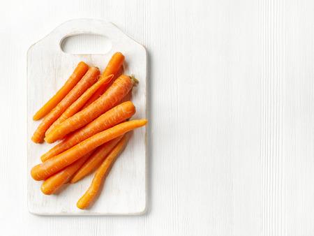 marchew: świeże surowe marchewki na białym drewnianym stole