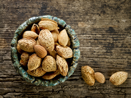 bowl of roasted almond nuts on old wooden table photo