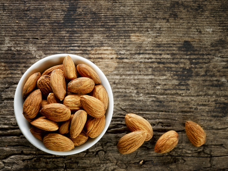 raw food: bowl of almond nuts on old wooden table Stock Photo