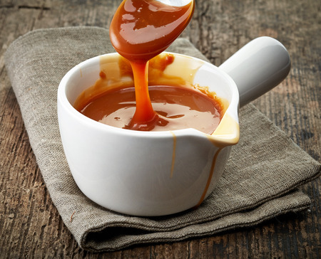 making: bowl of melted caramel sauce on old wooden table Stock Photo
