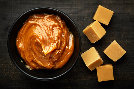 caramel candy: Bowl of melted caramel cream on black wooden table