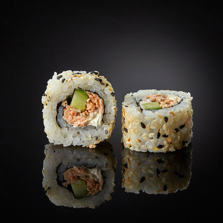 sushi menu: sushi with salmon and cucumber on black background