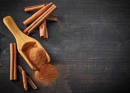 シナモンスティックと木製のテーブルに粉