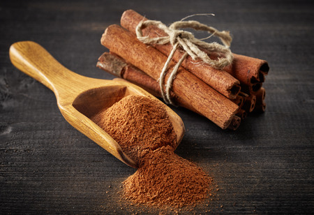 Cinnamon sticks and powder on wooden table Stock fotó