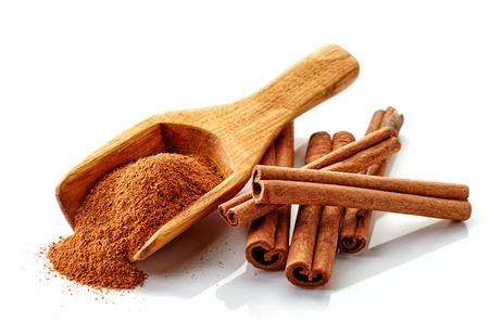 dry powder: cinnamon ground and sticks on a white background